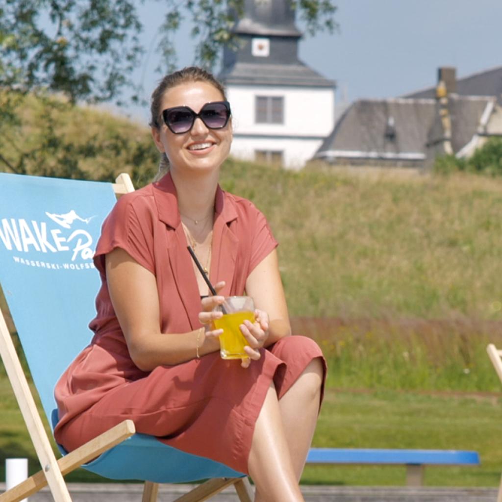 Ausschnitt des neuen Werbespots der WMG für den Tourismusstandort Wolfsburg, eine Frau sitzt mit einem Drink in einem Liegestuhl am Wakepark