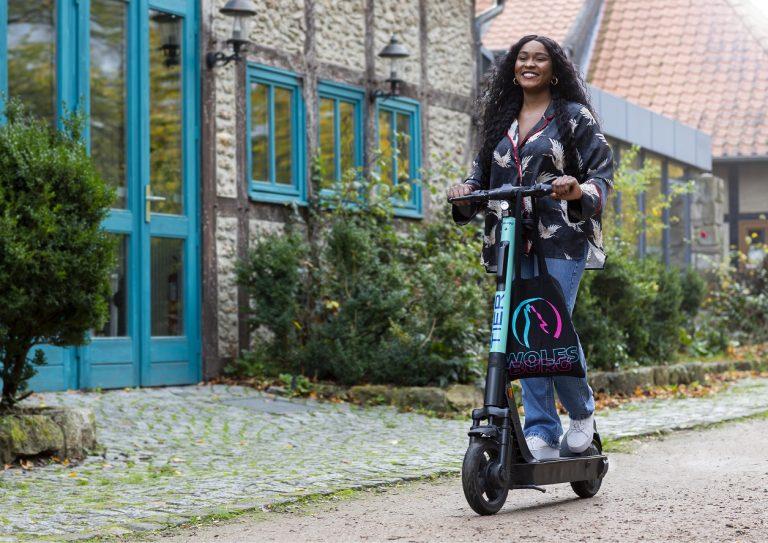 Eine Dame fährt auf einem E-Scooter von Tier durch Rothenfelde