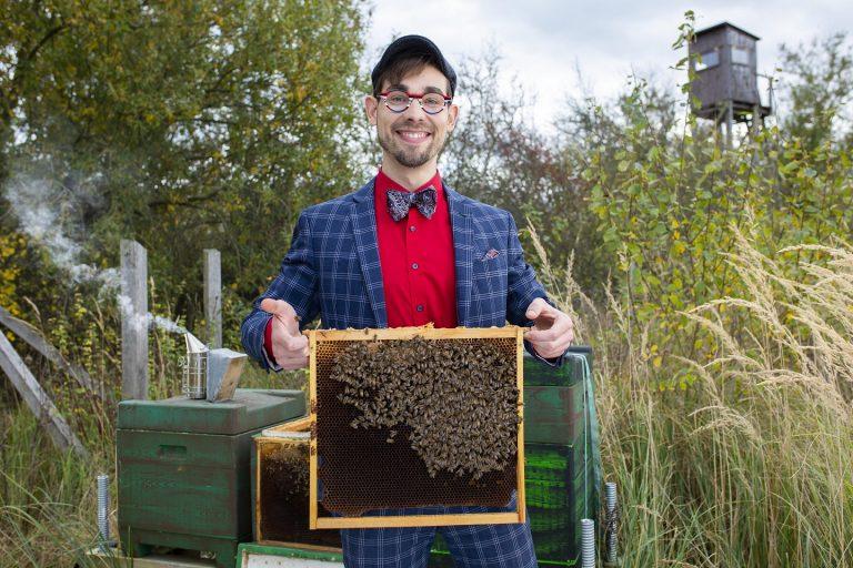 Ein lächelnder Mann mit einem Bienenstock in der Hand
