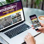 Neue Ausgabe des Wirtschaftsmagazins WOLFSBURG+ auf dem Desktop eines geöffneten Laptop und Smartphone