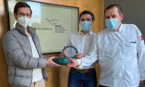 Tom Graubner und Carsten Gaedke vom Restaurant AWILON übergeben Jan-Hendrik Klamt, Prokurist und Bereichsleiter der WMG-Wirtschaftsförderung, eine Take-Away-Speise in der nachhaltigen Mehrschale REBOWL.