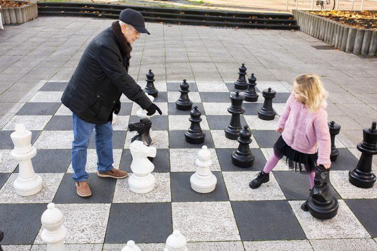 Ein älterer Herr spielt Schach mit einem kleinen Mädchen