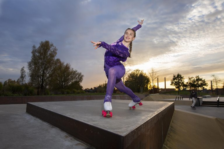 Ein Mädchen auf Rollschuhe posiert im Skatepark