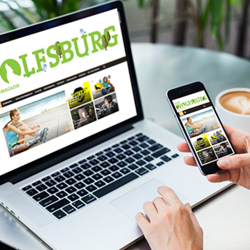 eue Ausgabe des Bürgermagazins DEIN WOLFSBURG auf dem Desktop eines geöffneten Laptop und Smartphone