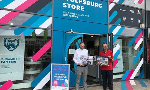 Christoph Kaufmann und Jens L. Heinrich präsentieren den Wolfsburger Benefizkalender 2022 vor dem Wolfsburg Store. Dort wird der Kalender verkauft.