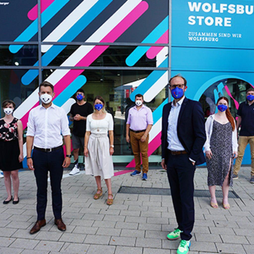 WMG Geschäftsführer und Belegschaft tragen FFP2-Masken der Wolfsburger Initiative Schenke ein Lächeln vor dem Wolfsburg Store. Dort werden die Masken zum Verkauf angeboten.